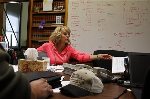 In this Nov. 6, 2013 photo, Washington County Commissioner Lea Ann Laybourn works in her office in the rural town of Akron, the county seat of Washington County, Colo. A day earlier, a majority in ...