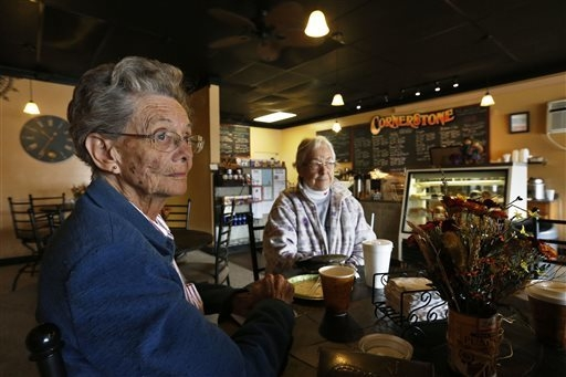 In this Nov. 6, 2013 photo, Pearl Gasser, age 80, sits with her friend Velma Drumtalk, at the Cornerstone Cafe, in the rural town of Akron, the county seat of Washington County, Colo. A day earlie ...