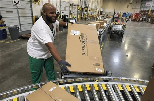 In this Nov. 11, 2010 file photo, Leacroft Green places a package to the correct shipping area at an Amazon.com fulfillment center, in Goodyear, Ariz. Amazon is teaming up with the U.S. Postal Ser ...