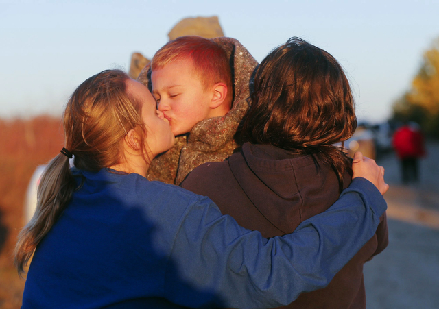 Reece Alexander, 6, gets a kiss as he is picked up by his relative after a bus accident sent the kids and bus into a creek Thursday, Oct. 31, 2013, in Butler County, Kan. The driver was taken to a ...