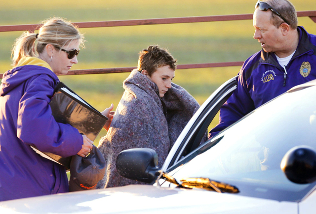 Logan Parker, 12, is put in a school security car after a bus accident sent the kids and bus into a creek Thursday, Oct. 31, 2013, in Butler County, Kan. The driver was taken to a hospital to be c ...