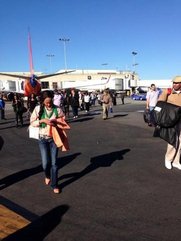 In this photo provided by Natalie Morin, people stand on the tarmac after being evacuated from Los Angeles International Airport, Friday, Nov. 1, 2013, in Los Angeles, after shots were fired at Te ...