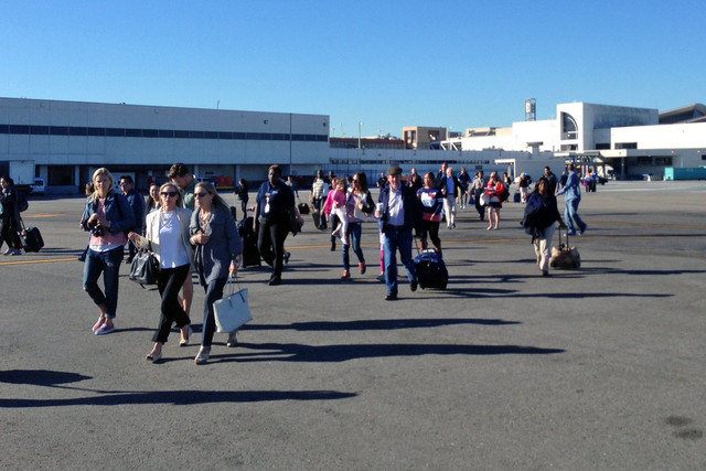 In this photo provided by John Forstrom, which has been authenticated based on its contents and other AP reporting, people walk across the tarmac after being evacuated from Los Angeles Internation ...