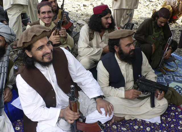 In this file photo taken Sunday, Oct. 4, 2009, new Pakistani Taliban chief Hakimullah Mehsud, left, is seen with his comrade Waliur Rehman, front center, during his meeting with media in Sararogha ...