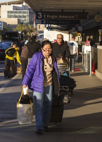 Departing passengers with their luggage arrive on Saturday, Nov. 2, 2013, at Los Angeles International Airport. A gunman armed with a semi-automatic rifle opened fire at the airport on Friday, kil ...