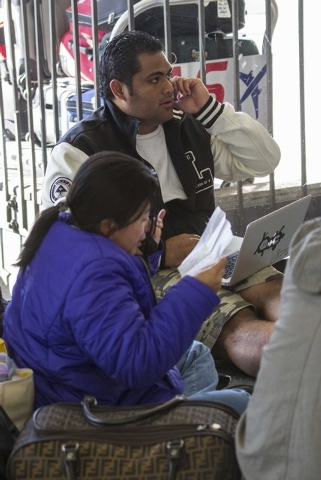 Passenger Tasi Lua, 25, right, of Hawaii, talks on the phone in Terminal 3 on Saturday, Nov. 2, 2013, at Los Angeles International Airport.  A gunman armed with a semi-automatic rifle opened fire  ...
