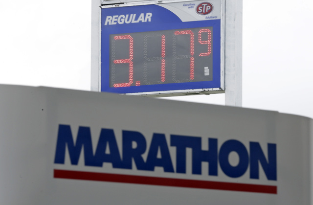 Gas prices drop to $3.17 at a Marathon station in Kokomo, Ind., Thursday, Oct. 24, 2013. Local gasoline prices are swinging up and down ever more drastically, a result of a national fuel system th ...