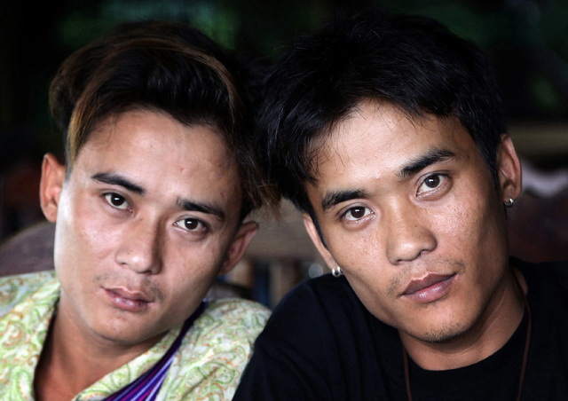 Johnny, left, and his twin brother Luther Htoo pose for photos after their reunion at a restaurant in Sangkhlaburi district of Kanchanaburi province, western Thailand. When they were kids, Johnny  ...