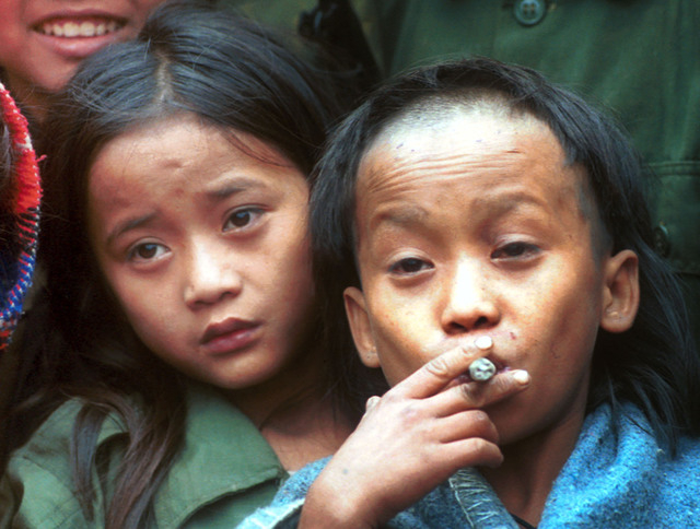 Johnny Htoo, left, a 12-year-old Karen boy, watches as his twin brother Luther smokes a Myanmar cigar during a meeting with The Associated Press at their jungle base of Ka Mar Pa Law in Myanmar op ...