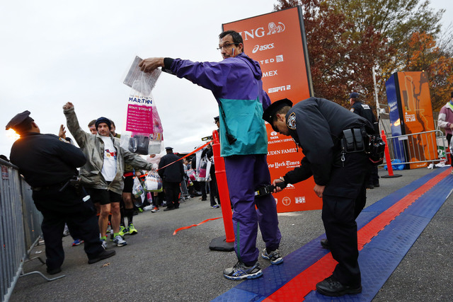 Runners are screened by police officers as they arrive at the start of the New York City Marathon, Sunday, Nov. 3, 2013, in New York. (AP Photo/Jason DeCrow)