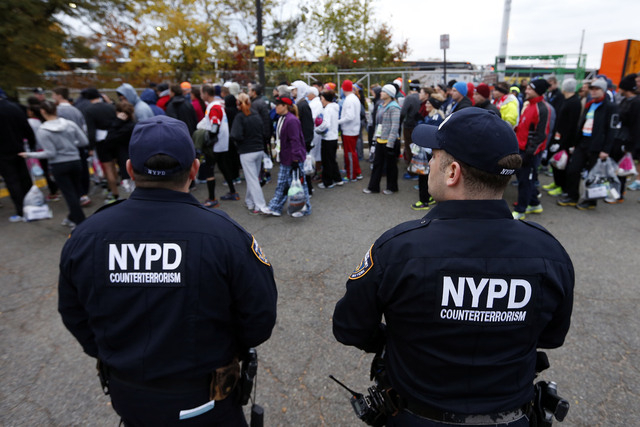 Police officers from the counterterrorism unit stand watch over runners who arrive for the New York City Marathon, Sunday, Nov. 3, 2013, in New York. (AP Photo/Jason DeCrow)