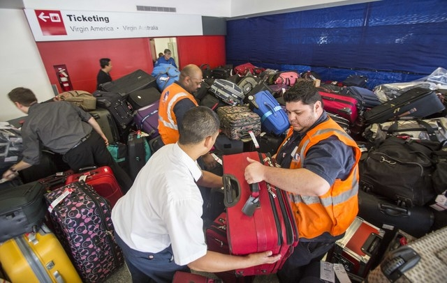 Transportation Security Administration employees classify the luggage to return to passengers at Los Angeles International Airport's Terminal 3 on Saturday, Nov. 2, 2013.  A gunman armed with a se ...