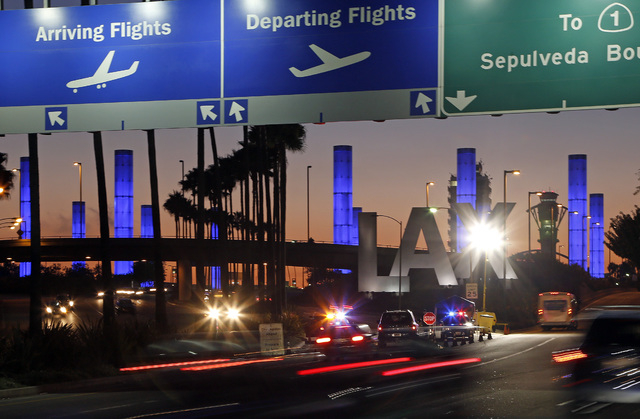 Lighted pylons at the Century Boulevard entrance to Los Angeles International Airport, which normally flash in a multicolored sequence, shine a steady blue Saturday evening, Nov. 2, 2013, in honor ...