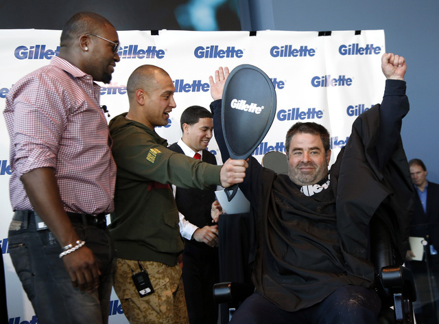 Boston Police Officer Steve Horgan raises his arms after being shaved along with Boston Red Sox baseball players David Ortiz, far left, and Shane Victorino, second from left, for One Fund Boston,  ...