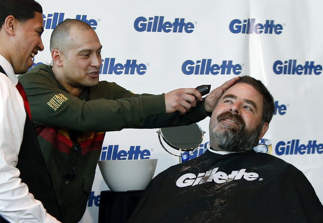 Boston Red Sox player Shane Victorino, center, kids around with a razor as Boston Police Officer Steve Horgan, right, is shaved for One Fund Boston, the Boston Marathon charity for bombing victims ...