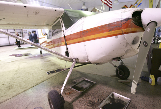 The plane that survived Saturdays midair collision sits in Skydive Superiors hanger, Sunday, Nov. 3, 2013, dripping oil. (AP Photo/The News-Tribune, Steve Kuchera)