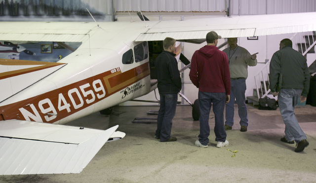 Two FAA investigators (right) meet with members of Skydive Superior on Sunday, Nov. 3, 2013 next to one of the planes involved in Saturdays midair collision. (AP Photo/The News-Tribune, Steve Kuchera)