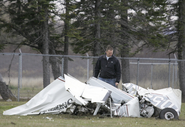 An FAA investigator Sunday, Nov. 3, 2013 examines the wreckage of a plane that crashed in Superior, Wis., Saturday after a midair collision with another plane. Both planes were carrying skydivers. ...