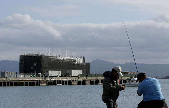 Two men fish in the water in front of a barge on Treasure Island in San Francisco. Google is erecting a four-story structure in the heart of the San Francisco Bay but is managing to conceal its pu ...
