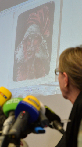 Expert and art historian Meike Hoffmann from the Berlin Free University looks at a projected painting of Otto Dix during a news conference in Augsburg, southern Germany, Tuesday, Nov. 5, 2013, on  ...