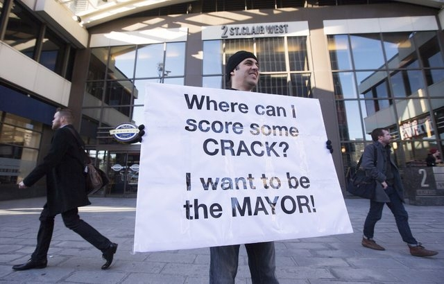Nic Bibassis holds a sign outside of where Toronto Mayor Rob Ford was talking on a radio show in Toronto, Sunday, Nov. 3, 2013. (AP Photo/The Canadian Press, Mark Blinch)