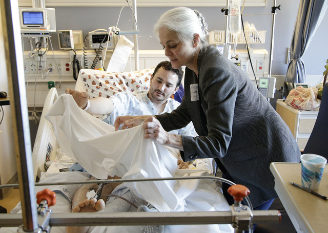 Judy Flaherty, right, covers her son Brian Ludmer with a bedsheet in his room at Ronald Reagan UCLA Medical Center on Tuesday, Nov. 5, 2013, in Los Angeles. Ludmer was the lone civilian wounded by ...