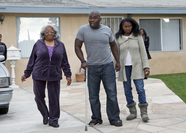 Transportation Security Administration officer Tony Grigsby  walks to meet reporters with his mother Faye Maye, right, and grandmother Juanita Davis at his home in Los Angeles Monday, Nov. 4, 2013 ...
