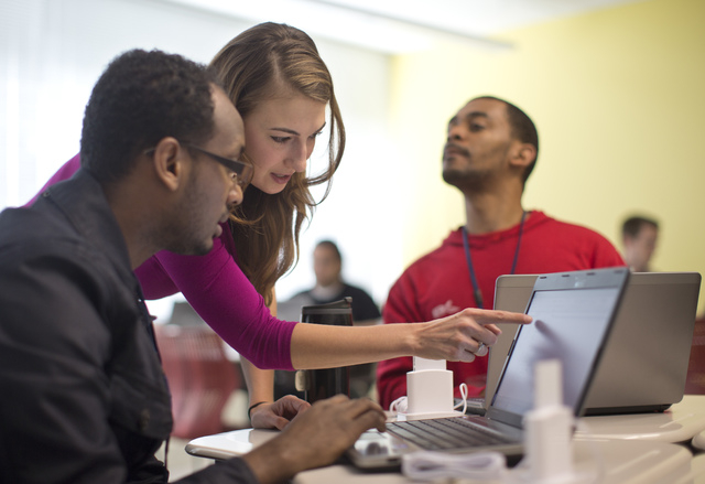 In this Oct. 22, 2013, photo, Kaylin Wainwright, center, works with student Natnael Gebremariam, left, at a computer during a General Educational Development test preparation class at the Sonia Gu ...