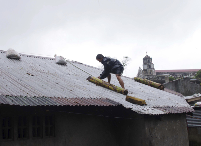 A man reinforces his house with banana stalks as powerful typhoon Haiyan hits Legazpi city, Albay province, about 325 miles south of Manila, Philippines on Friday. (AP Photo/Nelson Salting)