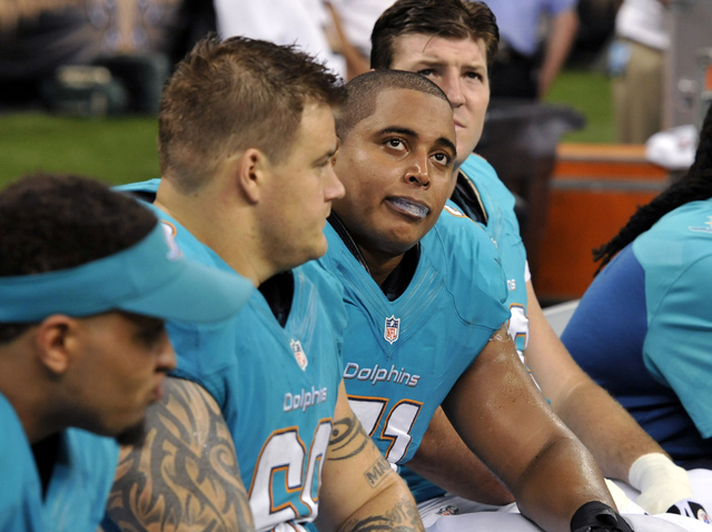 FILE - In this Sept. 30, 2013 file photo, Miami Dolphins guard Richie Incognito (68), center left, and  and tackle Jonathan Martin (71), center right, sit on the bench in the second half of an NFL ...