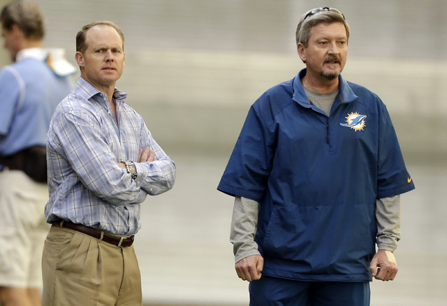 Miami Dolphins general manager Jeff Ireland, left, stands with head trainer Kevin O'Neill, right, during the NFL football team's practice Wednesday, Nov. 6, 2013, in Davie, Fla. (AP Photo/Lynne Sl ...