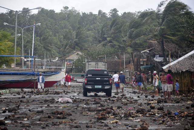 Debris litter the road by the coastal village in Legazpi city following a storm surge brought about by powerful Typhoon Haiyan in Albay province Friday, Nov. 8, 2013, about 520 kilometers ( 325 mi ...