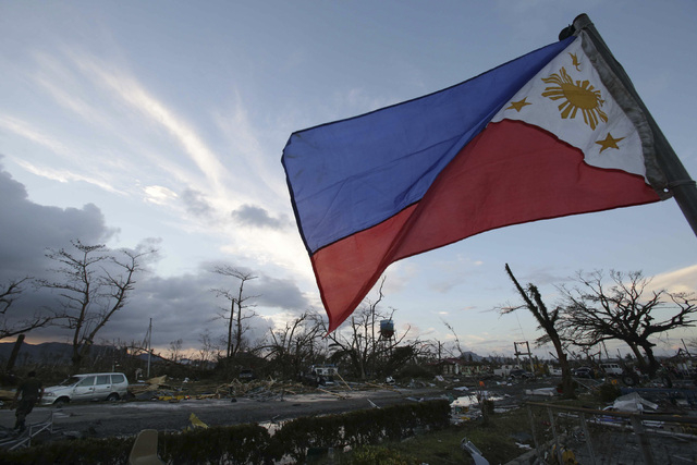 A Philippine flag stands amongst the damage caused after powerful Typhoon Haiyan slammed into Tacloban city, Leyte province, central Philippines on Saturday, Nov. 9, 2013. Rescuers in the central  ...