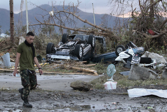 A Filipino trooper passes by toppled cars outside the airport terminal after powerful Typhoon Haiyan slammed into Tacloban city, Leyte province, central Philippines on Saturday, Nov. 9, 2013. Resc ...