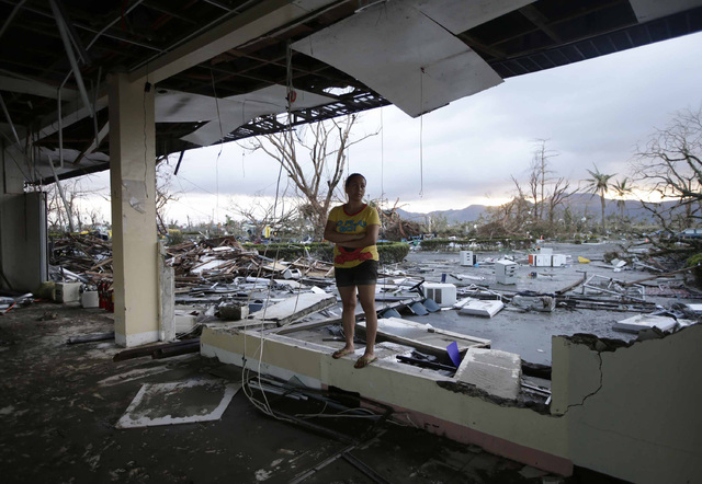 A woman stands amidst the devastation brought about by powerful Typhoon Haiyan at Tacloban city, in Leyte province, central Philippines Saturday Nov. 9, 2013. Rescuers in the central Philippines c ...