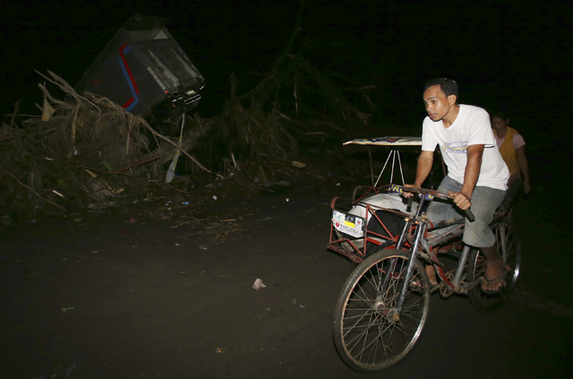 Survivor Sandy Torotoro pedals his pedicab along a dark street after powerful Typhoon Haiyan slammed into Tacloban city, Leyte province central Philippines on Saturday, Nov. 9, 2013.  The 44 year- ...