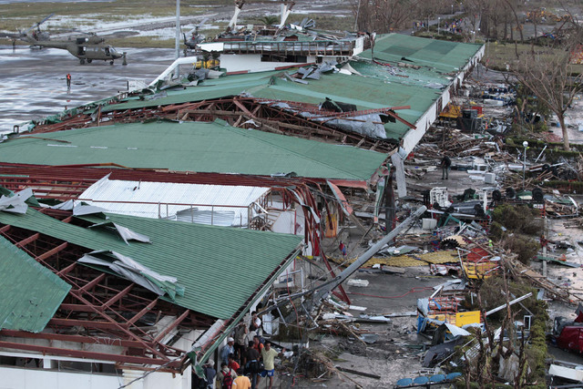 People stay outside the remains of a damaged airport terminal after powerful Typhoon Haiyan slammed into Tacloban city, Leyte province central Philippines on Saturday, Nov. 9, 2013. Rescuers in th ...