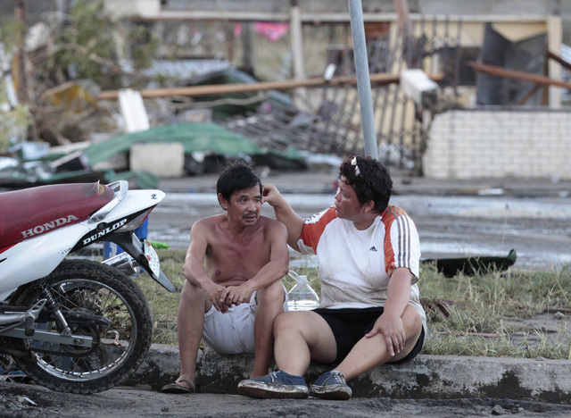 Residents sit outside their damaged house after powerful Typhoon Haiyan slammed into Tacloban city, Leyte province, central Philippines on Saturday, Nov. 9, 2013. The central Philippine city of Ta ...