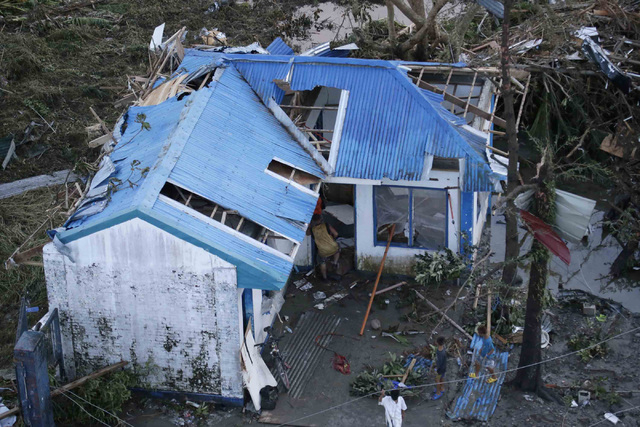 Residents sift through the rubble of their damaged house following a powerful typhoon that hit Tacloban city, in Leyte province, central Philippines Saturday, Nov. 9, 2013. The central Philippine  ...