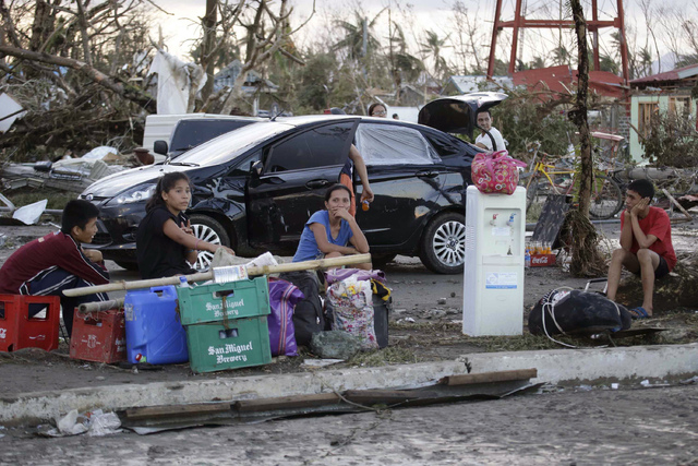 Residents sit amidst the rubble  Saturday Nov. 9, 2013, following  a powerful typhoon that hit Tacloban city, in Leyte province in central Philippines. Rescuers in the central Philippines counted  ...