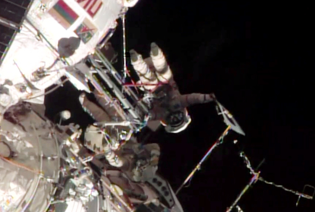 This screen image taken from NASA shows the Sochi Olympic torch being held during a spacewalk on Saturday, Nov. 9, 2013.  Video streamed by the US space agency NASA showed Oleg Kotov and Sergei Ry ...