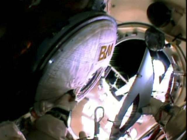 In this image taken from TV, the Olympic Torch is carried through a hatch as it is taken on a space walk from the International Space Station (ISS) Saturday Nov. 9, 2013. Two Russian cosmonauts Ol ...