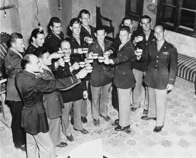 FILE - In this July 14, 1943 file photo, Maj. Gen. James Doolittle, (third from left, front row) who led the air raid on Japan, April 18, 1942, and some of the men who flew with him drink a champa ...