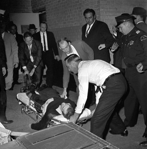 In this Sunday, Nov. 24, 1963 file photo, Lee Harvey Oswald, accused assassin of President John F. Kennedy, is placed on a stretcher after being shot in the stomach in Dallas. Nightclub owner Jack ...