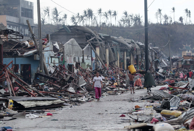 Residents walk past damaged structures caused by typhoon Haiyan,  in Tacloban city, Leyte province central Philippines on Sunday, Nov. 10, 2013. Haiyan, one of the most powerful typhoons ever reco ...