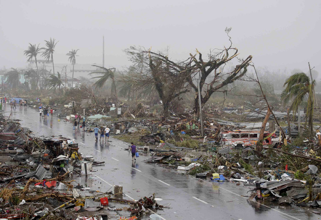 Resident walk past damaged houses in Tacloban city, Leyte province, central Philippines on Sunday, Nov. 10, 2013. The city remains littered with debris from damaged homes as many complain of short ...