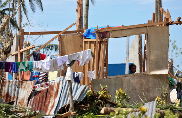 A resident sits her roofless house, after typhoon Haiyan hit the town, Sunday, Nov. 10, 2013, in Daanbantayan town, north Cebu, central Philippines. Typhoon Haiyan, one of the most powerful storms ...