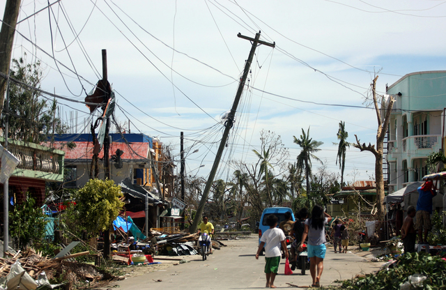 Residents walk past the devastation caused by Typhoon Haiyan, Sunday, Nov. 10, 2013, in Daanbantayan town, north Cebu, central Philippines. Typhoon Haiyan, one of the most powerful storms on recor ...