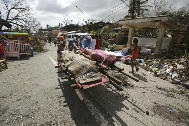 Residents push dead bodies on a cart after strong waves caused by Typhoon Haiyan slammed into Tacloban city, Leyte province central Philippines on Sunday, Nov. 10, 2013. Typhoon Haiyan, one of the ...