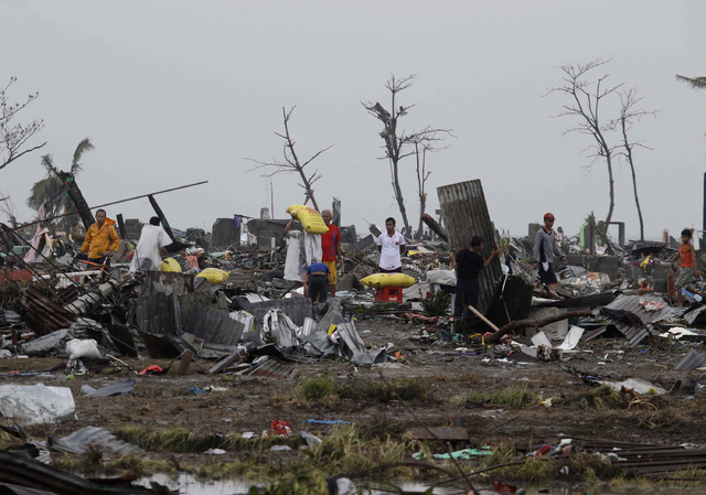 Residents salvage belongings from their damaged houses in Tacloban city, Leyte province, central Philippines on Sunday, Nov. 10, 2013. The city remains littered with debris from damaged homes as m ...